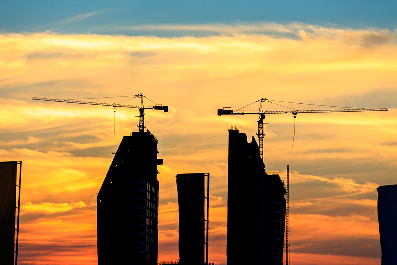 Silhouette of a building under construction with a magnificent sunset background in Dubai, UAE.