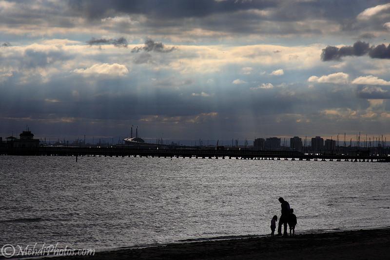 Family gathering under rays of light, St Kilda Beach, Melbourne, AU.