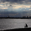 Family gathering under rays of light, St Kilda Beach, Melbourne, AU.