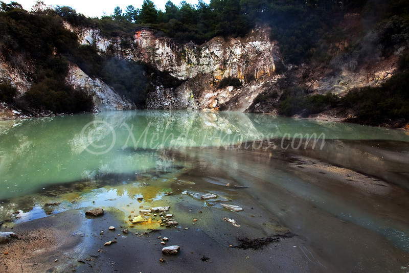Wai-O-Tapu, New Zealand, Alum Cliffs: The track winds its way past cliffs of alum. Shallow horizontal ridges indicate ancient weathering, the eruption crater opposite with its acidic lake is about 700 years old.