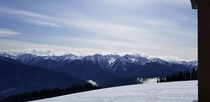 The view from on top of Hurrican Ridge looking out to the majestic snow-covered mountain scenes. No matter the direction you look, your view is filled with awe-inspiring visions. Over the ridge, small cloud banks play peek-a-boo.