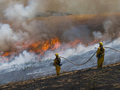 Firefighters monitor the burn