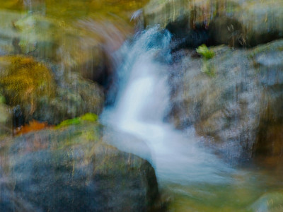 Impression of water tumbling over stones in Purisima Creek.   I moved the camera during a long exposure.