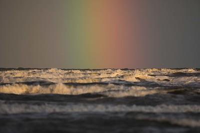 Skurar över havet i morgonsolen, regnbåge.