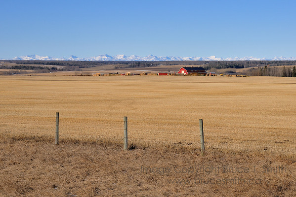 Early spring view of a prairie farm with the Rocky Mountains in the background.