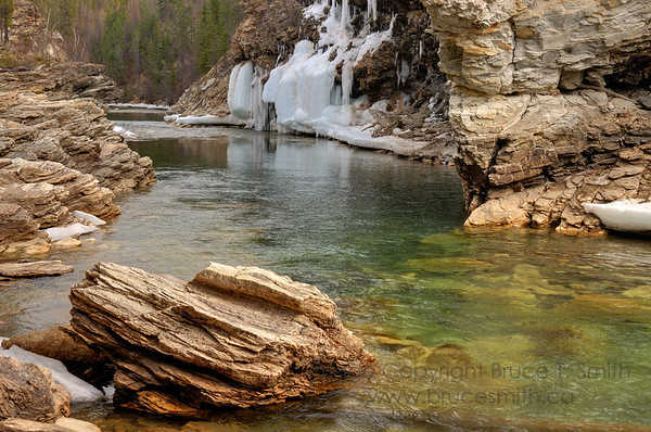 Mountain stream and frozen waterfall in springtime