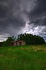 Storm clouds gathering over abandoned farm buildings