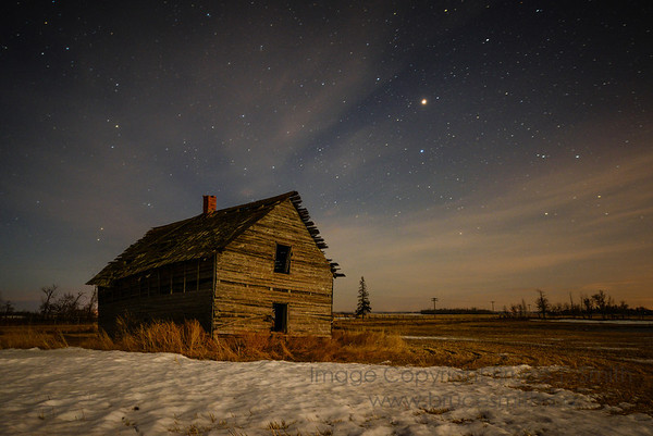 An old abandoned wooden farmhouse in the moonlight, under a starry sky, with Mars almost at opposition to the sun.