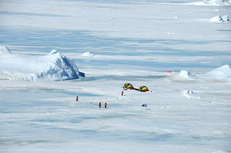 That's base camp as seen from the helicopter.  In order to cause as little disruption as possible, base camp is set up at least a mile from the rookery with the helicopter landing site located behind an iceberg. On past trips, it was no problem finding suitable base camp locations, but the rapidly deteriorating ice sheet this year made the job quite difficult.