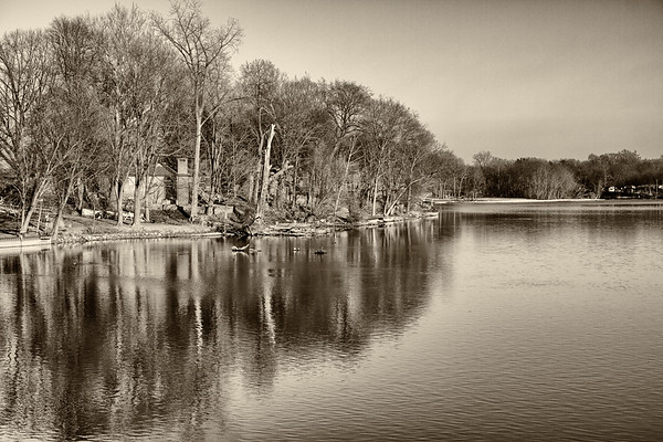 Houses in the trees on the banks of a river in winter - Sepia layer