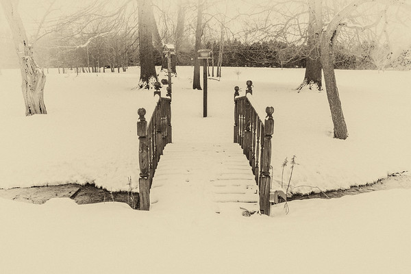 Bridge over snow and stream - leading lines - sepia with white vignette