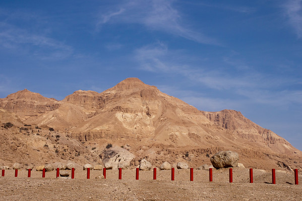 Red poles under a mountain in the Judean desert