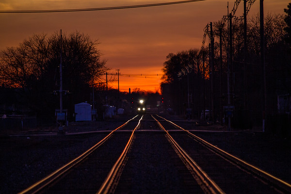 Train approaching on the tracks dark red sunset