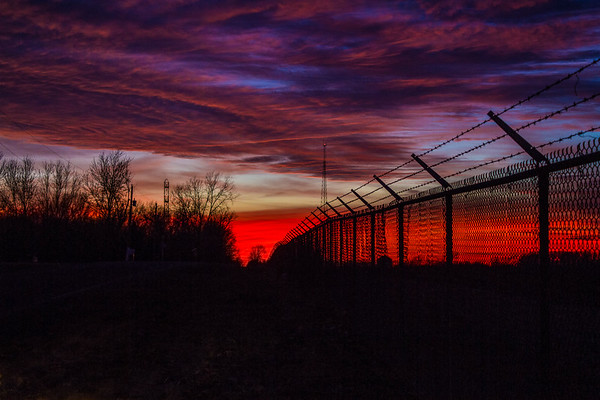 Barbed wire and fence going into red sunset