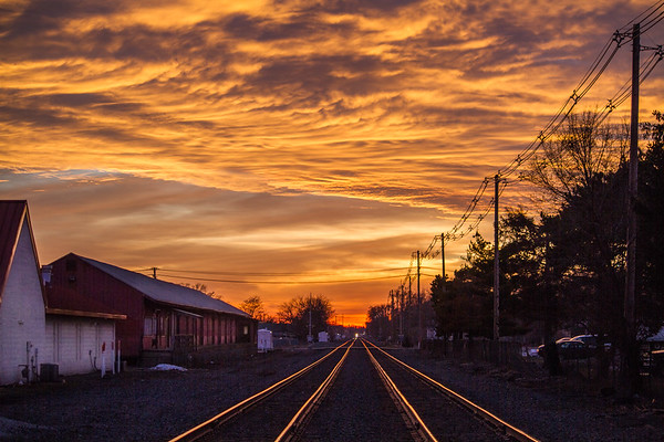 Train tracks glowing during sunset - oncoming train afar - 2