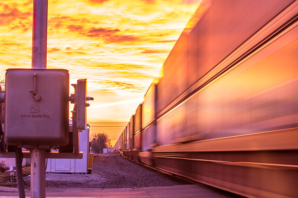Train rolling by at fiery sunset - landscape