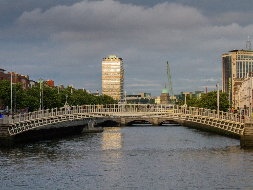 Dublin - Ha'Penny bridge over Liffy River with buildings in background