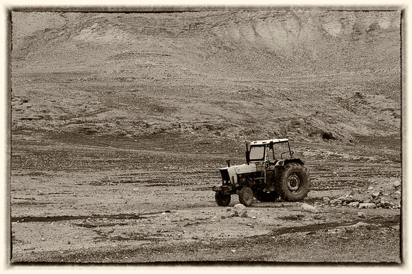 Tractor at the base of a hill B-W