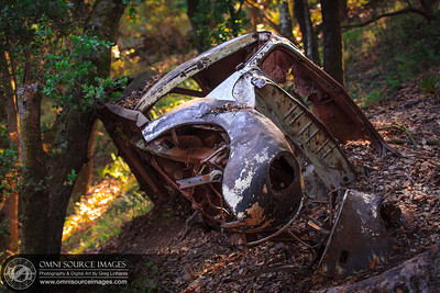 An old Volkswagen wreck rests above a popular hiking trail in the Oakland Hills.