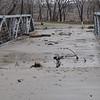 Debris carried by water from creek overflowing bridge
