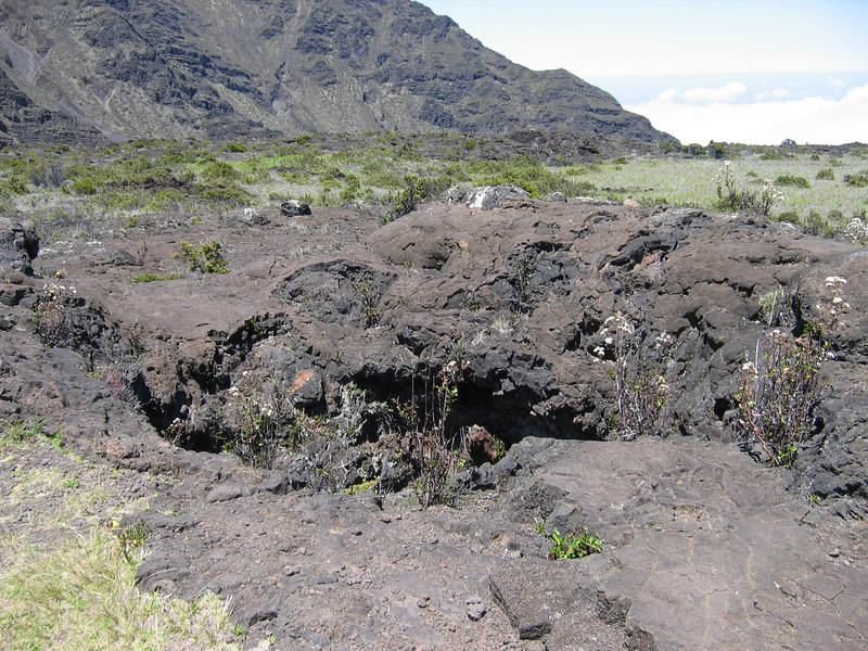 when you see this hole in the ground, turn around, walk 30 feet, and the lava tube side trail is on your right . . .enjoy!