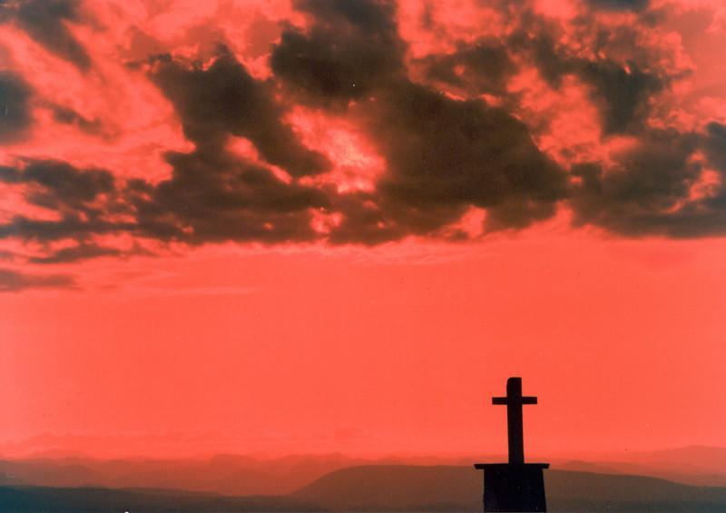 Kariba Cross: The cross of a church building stands in silhouette against the hills of the Zambesi River escarpment in Kariba, Zimbabwe, Africa