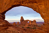 Turret Arch is visible through the North Window at sunrise in Arches National Park.