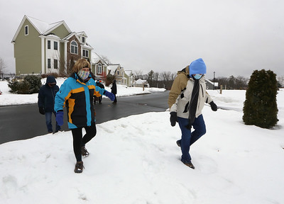 Dracut Land Trust's annual Town of Dracut birthday hike, on Tranquility Trail from Broadway Road. Sherrie Ninteau, left, and Marianne Blanchet, both of Dracut, head over snow to resume the trail. (SUN/Julia Malakie)
