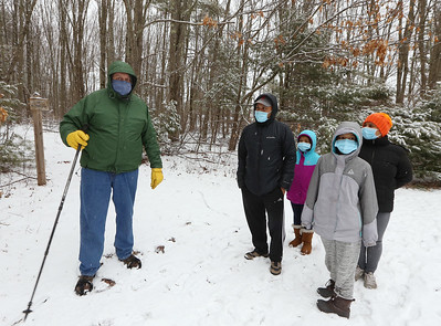 Dracut Land Trust's annual Town of Dracut birthday hike, on Tranquility Trail from Broadway Road. Open Space Committee chairman Dave Sutherland of Dracut, left, welcomes Pawan Shrestha, his wife Maushami, right, and daughters Ritu, 10, front, and Isha, 8, rear, of Waltham. Pawan Shrestha said they love to drive to walks to get to know other towns, and heard about this one on Facebook.(SUN/Julia Malakie)