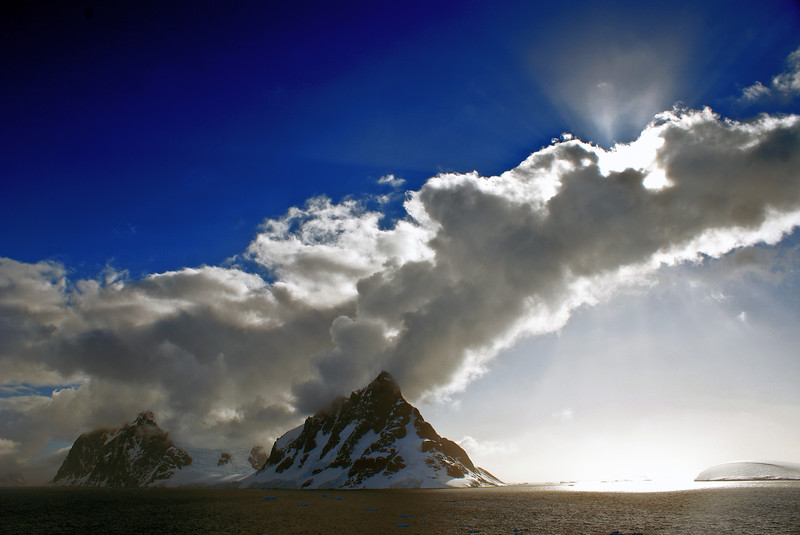 Dramatic clouds with snow capped mountains, glaciers and ocean taken at lemmair channel, antarctica