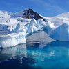 Beautiful iceberg in crystal clear waters at Antarctica on a sunny day.