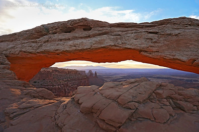 Mesa Arch with the sunrise casting a glow from the walls below the arch.