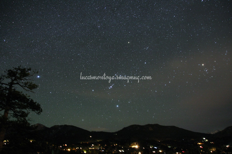 Constellation Orion setting in the west over Estes Park; Aldebaran is the bright star on the far right, Sirius is the bright star on the far left; some clouds — in Estes Park, Colorado.