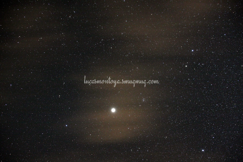 Jupiter, with Beehive Cluster to its right; high clouds are orangeish in this photo and diffuse the light of the objects behind it — in Estes Park, Colorado.