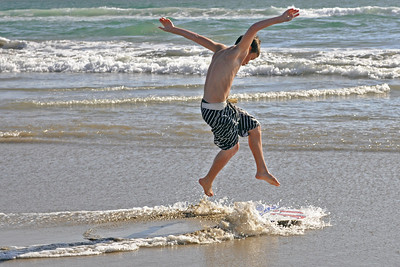 Flight - A young man practices his technique on the skimboard.
