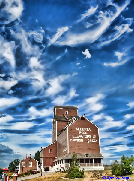 """Dawson Creek Art Gallery, Mile Zero, Alaska Highway.  In 1947 Dawson Creek was the largest grain producer in the British Empire, and by 1950 8 grain elevators lined up along the Alaska Highway.  This one was built by the Alberta Wheat Pool in 1948. However, by 1980 6 of the elevators had been replaced by modern concrete ones, and all across the prairies the wooden structures that had stood for 100 years were disappearing.  The Alberta Wheat Pool sold """"Elevator #2"""" to the city of Dawson Creek for $1.00, and it was moved to it's present location.  The Art Gallery opened in 1983."""