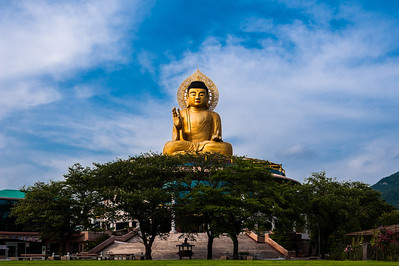 Buddha is over 50 feet tall sitting on top of a temple.