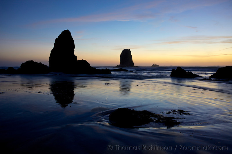The crescent moon hangs above the serene sands of Cannon Beach, a beautiful blue evening with the silhouette of the Needles at Haystack Rock on the Oregon Coast.