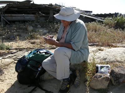 Atop Caliente Peak, signing the peak register. Surprising to me, this tiny notebook carried several years worth of entries; we found our previous entry from 2008 just a few pages prior to where we signed this time.