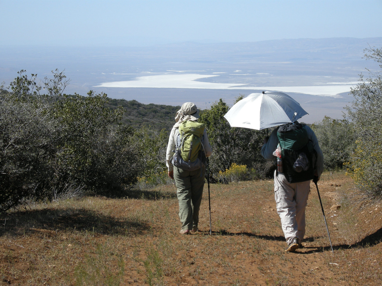 Getting near the end of the hike, with Sam taking his turn under the aluminized umbrella; it makes a substantial difference in how hot you get. Ahhh, cool shade! Soda Lake is in the background, and at this point we're about a mile from the trailhead and our car. A nice little hike!