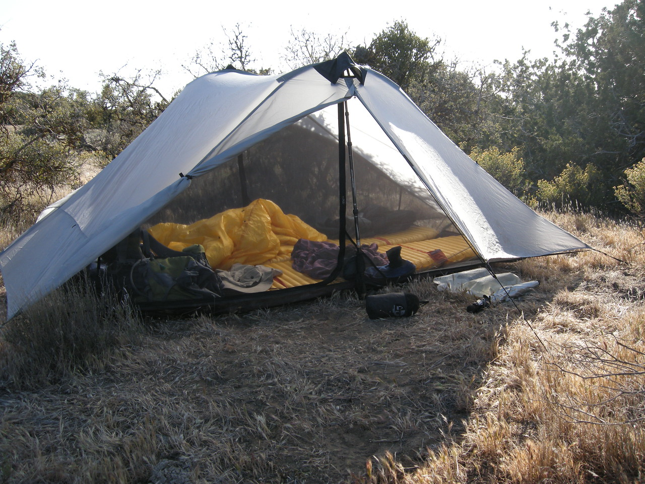 Our Six Moon Designs Lunar Duo, with Ray Jardine quilt and dual Thermarest NeoAir mattresses. Two hiking poles hold up the tent. Additional water pouches beside the tent; this trail is dry and you must carry all your water.