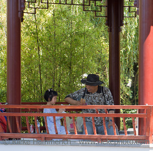 Vancouver, British Columbia, Canada – August 6, 2005: Grandfather and Granddaughter resting in Pagoda in Dr. Sun Yat-Sen Classical Chinese Garden in Vancouver, Canada. Dr. Sun Yat-Sen Classical Chinese Garden was built using the principles and techniques of the original Ming Dynasty Garden and opened 1986. The design is based on the harmony of the four main elements rock, water, plants, and architecture. They combine to create an experience of perfect balance.