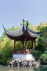 Vancouver, British Columbia, Canada – August 6, 2005: Pagoda with Chinese Family in Dr. Sun Yat-Sen Classical Chinese Garden in Vancouver, Canada. Dr. Sun Yat-Sen Classical Chinese Garden was built using the principles and techniques of the original Ming Dynasty Garden and opened 1986. The design is based on the harmony of the four main elements rock, water, plants, and architecture. They combine to create an experience of perfect balance.
