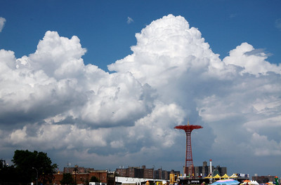 The parachute tower is a prominent feature on the boardwalk at Coney Island.  Symmetry of the clouds and tower was interesting.