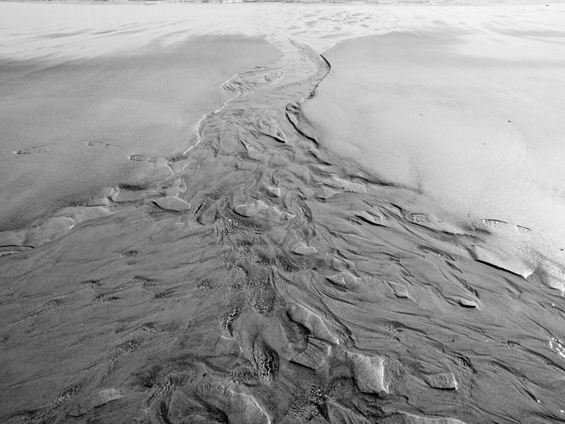 B&W conversion to enhance the pattern of sand and water.  Seabrook Beach, NH