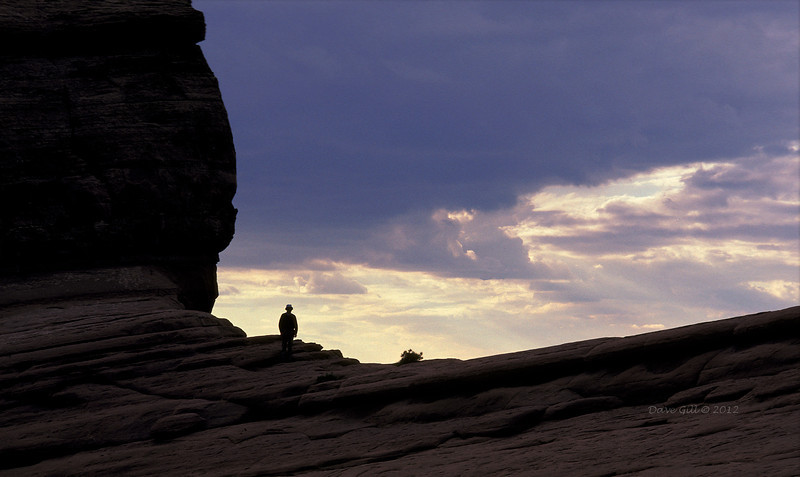 A lone hiker silhouetted at dusk in Arches National Park, Utah.