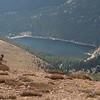 Marmot on a rock overlooking a mountain lake.