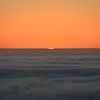 The sun sets behind the fog-covered Pacific Ocean.