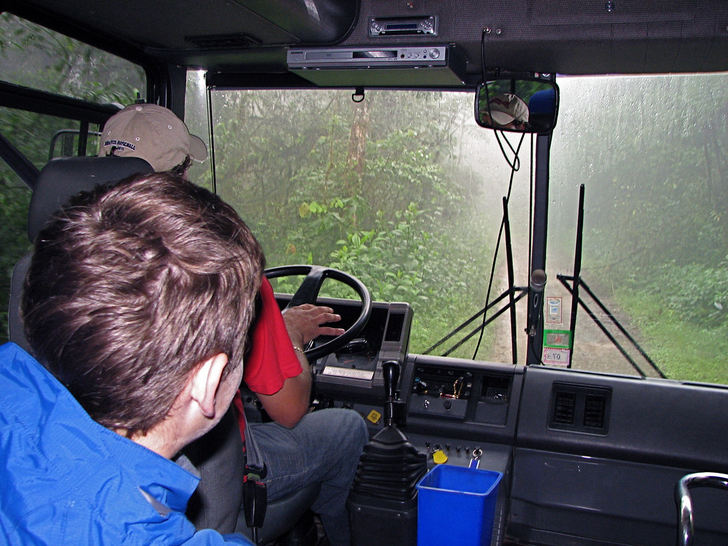 View out bus windshield of a rainy foggy road through a Costa Rican rainforest