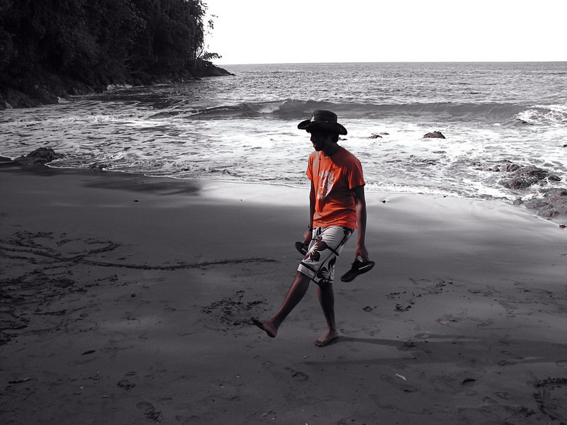 Photographic trick: color replacement that turned everything other than this guys orange shirt to shades of gray.  On the beach at Campanario, Osa Peninsula, Costa Rica.
